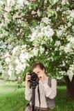 在照相机的妇女射击在monopod 免版税库存图片