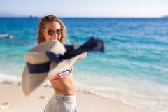 在照相机的美丽的少妇投掷的帽子在海滩 库存照片