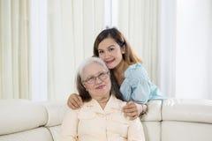 在照相机的老妇人微笑与她的女儿 图库摄影