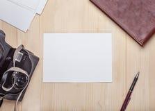 在照相机围拢的一张木桌上的空白的照片卡片,册页, 库存图片