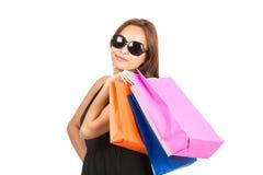 在照相机H的购物的亚裔妇女五颜六色的袋子 库存照片