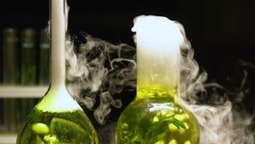 在煮沸的烧瓶的化工液体散发在黑暗的背景的烟,提取 影视素材