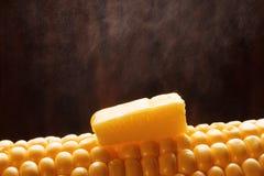 在煮沸的玉米的黄油 库存图片