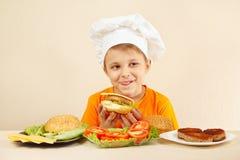 在煮熟的汉堡包附近被舔的小滑稽厨师开胃 免版税库存图片