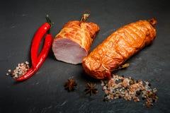 在熏制的腌火腿片断的顶视图用香料和两辣椒 免版税库存照片