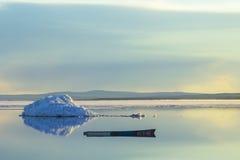 在熔化的冰山的背景的一条老小船在春天山湖的落日的 库存照片