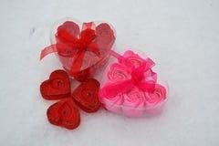 在熔化雪的红色和桃红色心脏 以心脏的形式三个红色蜡烛 图库摄影