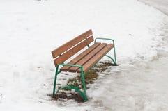 在熔化雪的长凳 免版税库存图片