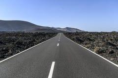 在熔岩杆中的柏油路在兰萨罗特岛加那利群岛 库存图片
