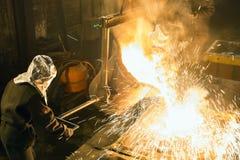 在熔炉的工作者控制金属熔化 工作者在冶金植物经营 液体金属倾吐 免版税库存照片