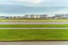 在燃料贮存坦克和工业储藏地前面的机场跑道 库存图片