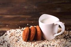 在燕麦背景的麦甜饼,在一杯牛奶旁边,在葡萄酒板 免版税库存图片