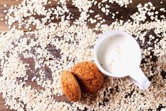 在燕麦背景的麦甜饼,在一杯牛奶旁边,在葡萄酒板 免版税图库摄影