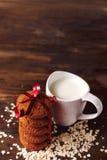 在燕麦背景的麦甜饼,在一杯牛奶旁边,在葡萄酒板 库存图片