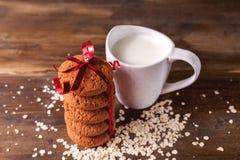 在燕麦背景的麦甜饼,在一杯牛奶旁边,在葡萄酒板 图库摄影