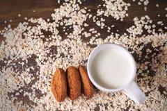 在燕麦背景的麦甜饼,在一杯牛奶旁边,在葡萄酒板 免版税库存照片