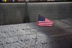 在爆心投影曼哈顿的纪念品9月11日与站立在受害者附近Engra的名字的一面美国国旗的恐怖袭击的 免版税库存照片