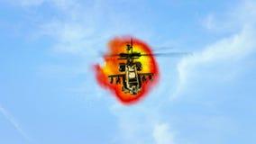 在爆炸前面的直升机飞行 免版税库存照片