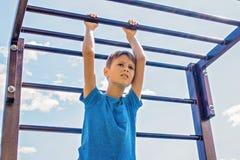 在爬升套架的孩子训练在操场户外 图库摄影
