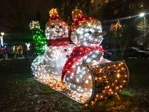 在爬犁的Iluminaning snowmans 库存照片