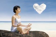 在爱云彩下的有吸引力的妇女锻炼瑜伽在海滩 免版税库存图片