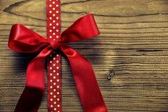 在爱墙纸-在木背景的大红色弓 免版税库存图片