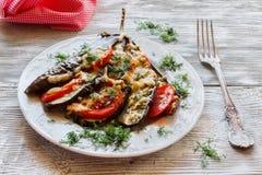 在爱好者形状的被烘烤的茄子在一把白色板材和葡萄酒叉子 木背景 烹调用蕃茄和乳酪 图库摄影