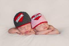 在爱妈妈和爸爸帽子的新出生的婴孩孪生 免版税库存图片