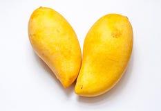 在爱心脏位置孤立白色backgr的成熟大黄色芒果 免版税图库摄影