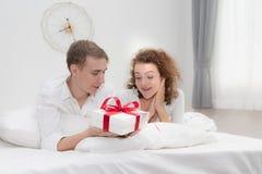 在爱惊奇礼物盒的年轻夫妇在卧室,庆祝情人节 免版税库存图片