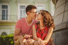 在爱感人的鼻子的逗人喜爱的年轻微笑的夫妇,拥抱,坐户外在绿色城市街道,夏令时 免版税库存照片