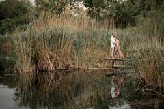 在爱拥抱和亲吻的夫妇在木码头在村庄 免版税库存图片
