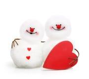 在爱拥抱的两个逗人喜爱的雪人 免版税库存图片