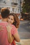 在爱拥抱的美好的年轻微笑的夫妇,坐户外在绿色城市街道,夏令时 人松劲和妇女我 免版税图库摄影