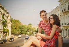 在爱拥抱的逗人喜爱的年轻微笑的夫妇,坐户外在绿色城市街道,夏令时 女孩佩带杯她的boyfr 免版税图库摄影