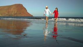 在爱无忧无虑走的夫妇从在海滩的水 特内里费岛, Canarian海岛美丽如画的海洋海岸  影视素材