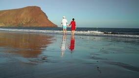 在爱无忧无虑走的夫妇到在海滩的水 特内里费岛, Canarian海岛,西班牙美丽如画的海洋海岸  影视素材