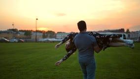 在爱滑稽旋转的愉快的夫妇在夏天晚上日落公园 影视素材