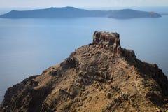 在爱琴海的背景的一个大岩石 从圣托里尼海岛的看法  库存照片