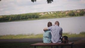 在爱的一对夫妇在日期坐在河前面的一张桌 人拥抱女孩 小犬座坐在旁边 影视素材