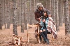 在爱的一对夫妇在森林,女孩喝茶,人皮有一条温暖的毯子的一个女孩从后面 免版税库存照片