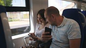 在爱的一对夫妇在看照片的舒适的椅子坐智能手机 在旅行的爱的一对夫妇  影视素材