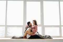 在爱的一对夫妇坐窗台 获得的新婚佳偶乐趣 图库摄影