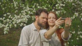 在爱的一对夫妇看在智能手机屏幕上的照片并且采取selfie 股票视频