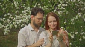 在爱的一对夫妇看在智能手机屏幕上的照片并且采取selfie 影视素材