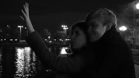 在爱的一对夫妇站立反对夜城市的光在江边 在河附近的惊人的婚礼夫妇在晚上 免版税图库摄影