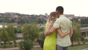 在爱的一对年轻夫妇站立拥抱在公园和看美丽的景色 股票视频