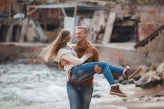 在爱的一对年轻夫妇在海滩在秋天 库存图片