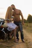 在爱的一对年轻夫妇在领域的一辆摩托车 免版税库存照片