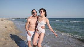 在爱的假期夫妇在赤足走在沙子,海滩全景,愉快的朋友的异乎寻常的海岛、恋人人和女孩上 股票视频